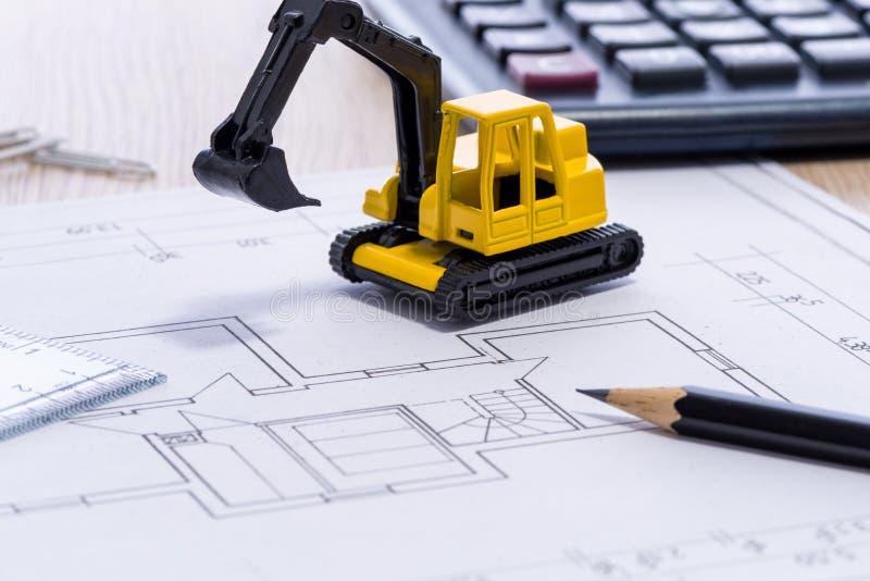 Desktop com máquina escavadora, régua e lápis do amarelo do modelo a mini imagens de stock