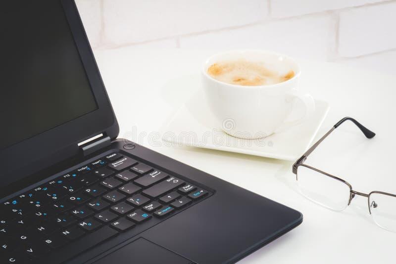 Desktop com portátil, vidros do olho e uma xícara de café foto de stock