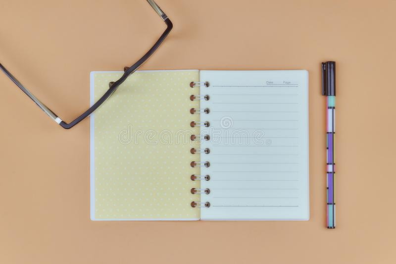 Desktop com vidros, uma folha branca para o texto, um caderno do escritório, uma pena na cor do fundo delicado Vista superior com imagens de stock