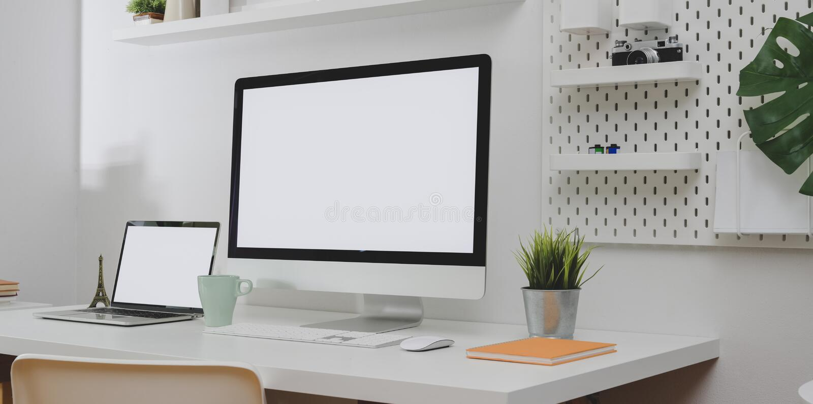Desktop computer and blank screen laptop with copy space and office decorations in minimal white office room royalty free stock photo