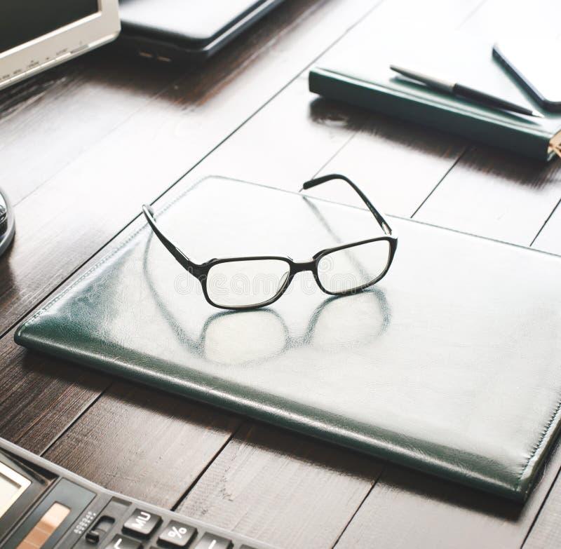 Desktop con spirito di cuoio della cartella, di vetro, del calcolatore e del blocco note fotografie stock