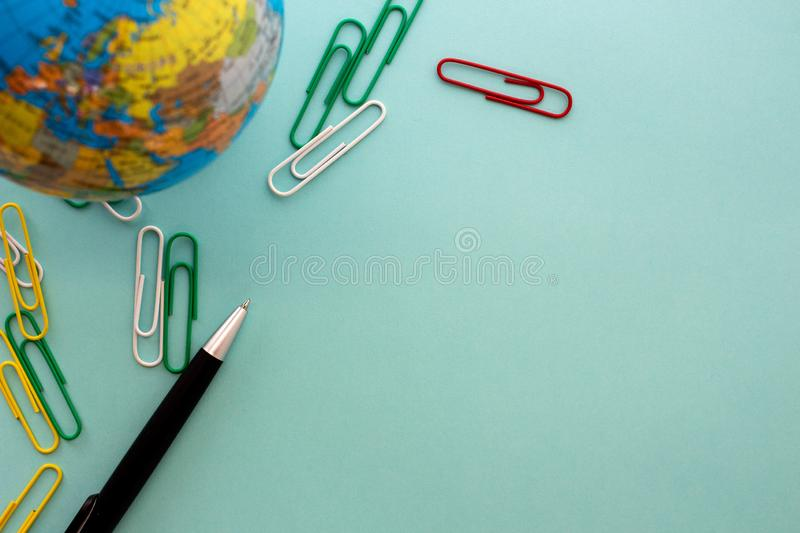 Desktop design with globe, colorful metal paperclips and black pen in flat lay design stock image
