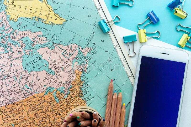 Desktop design of Map of Canada, Greenland and the North of America with colorful paperclips, colored pencils and mobile phone stock photography