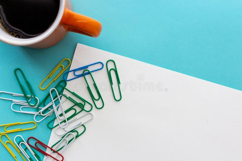 Desktop design with orange mug of coffee and colorful paperclips stock image