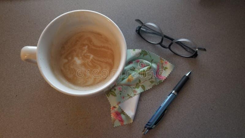 Desktop dostawy dla pracy zawierają pióro, chusteczka, oczu szkieł esspresso latte w białym filiżanka ariela widoku zdjęcia royalty free