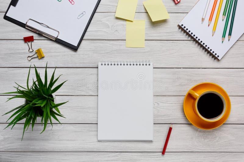 Desktop filiżanki kawy ołówków majcherów białe żółte notatki i notepad klawiaturowy odgórny widok kwitną zdjęcie stock
