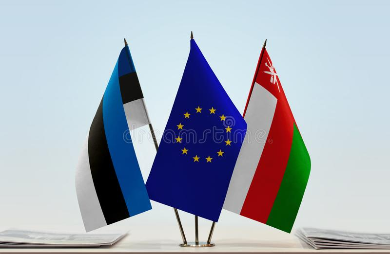 Flags of Estonia EU and Oman. Desktop flags of Estonia and Oman with European Union flag in the middle royalty free illustration