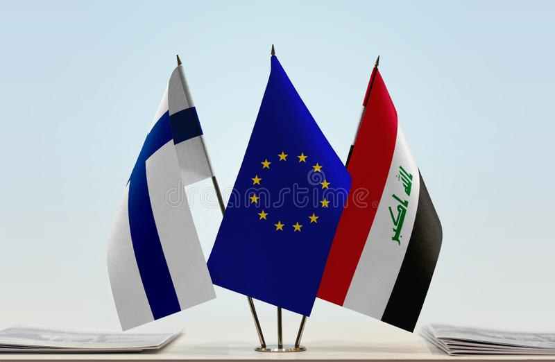 Flags of Finland EU and Iraq. Desktop flags of Finland and Iraq with European Union flag in the middle stock photos