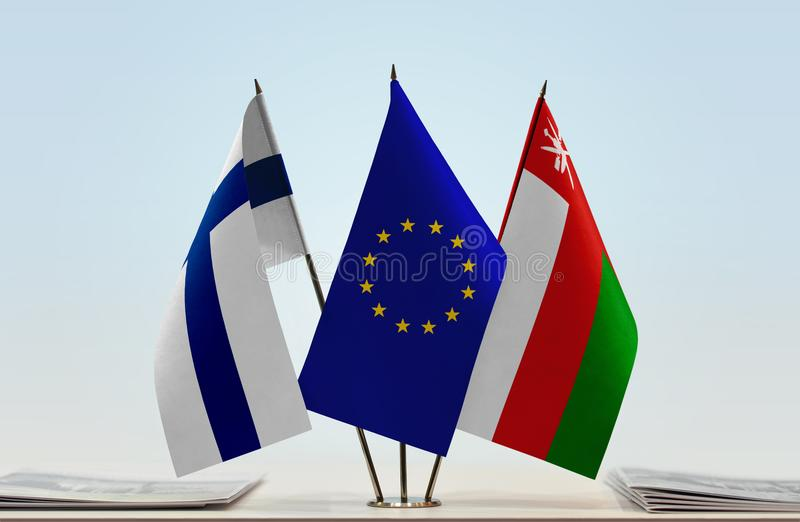 Flags of Finland EU and Oman. Desktop flags of Finland and Oman with European Union flag in the middle stock photo