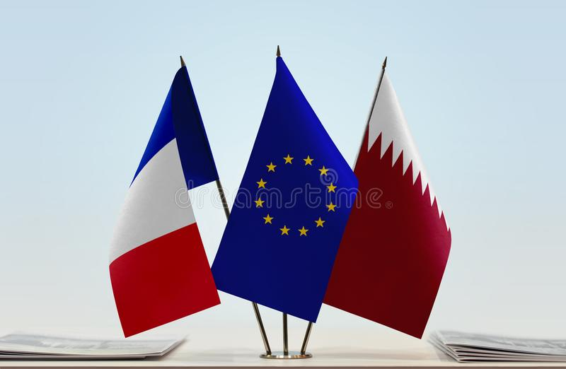 Flags of France EU and Qatar. Desktop flags of France and Qatar with European Union flag in the middle royalty free stock photography
