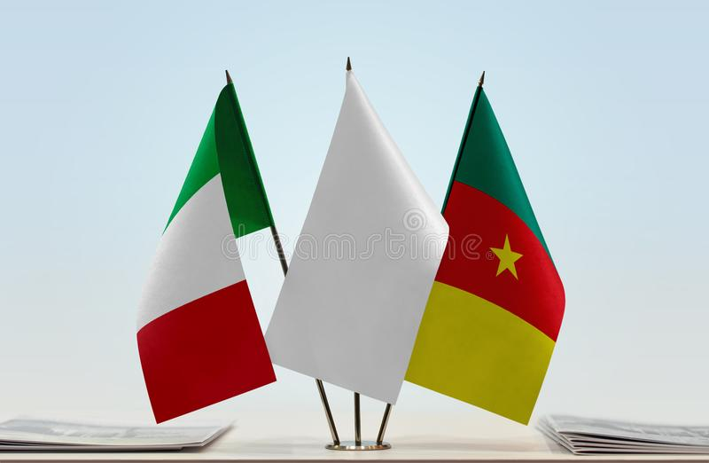 Flags of Italy and Cameroon. Desktop flags of Italy and Cameroon with white flag in the middle royalty free stock photo