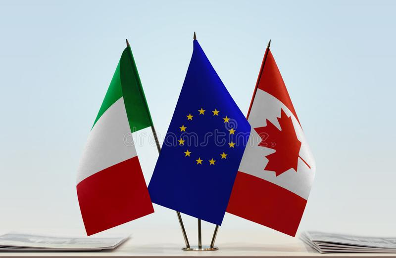 Flags of Italy EU and Canada. Desktop flags of Italy and Canada with European Union flag in the middle royalty free stock image