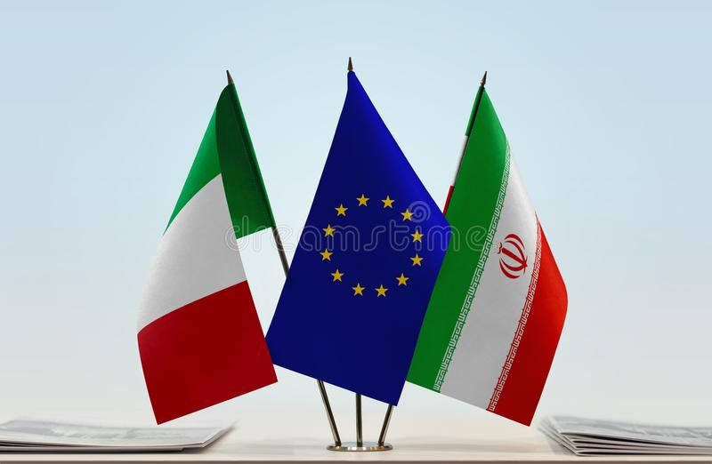 Flags of Italy EU and Iran. Desktop flags of Italy and Iran with European Union flag in the middle stock photography
