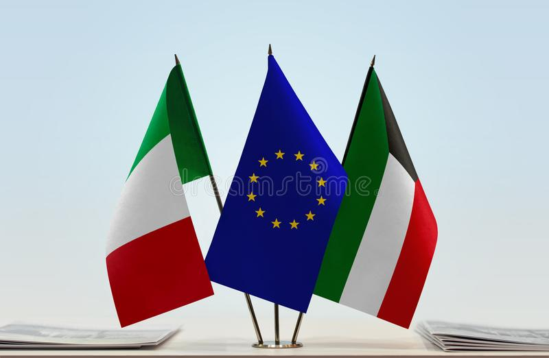 Flags of Italy EU and Kuwait. Desktop flags of Italy and Kuwait with European Union flag in the middle stock image
