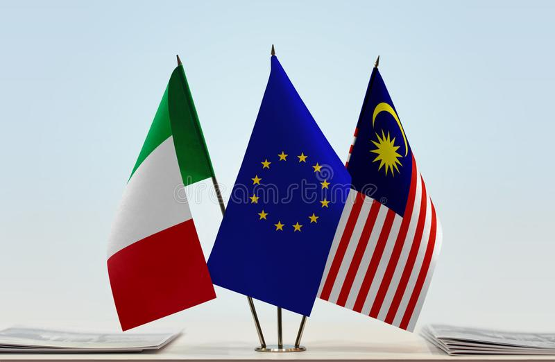 Flags of Italy EU and Malaysia. Desktop flags of Italy and Malaysia with European Union flag in the middle royalty free stock photography