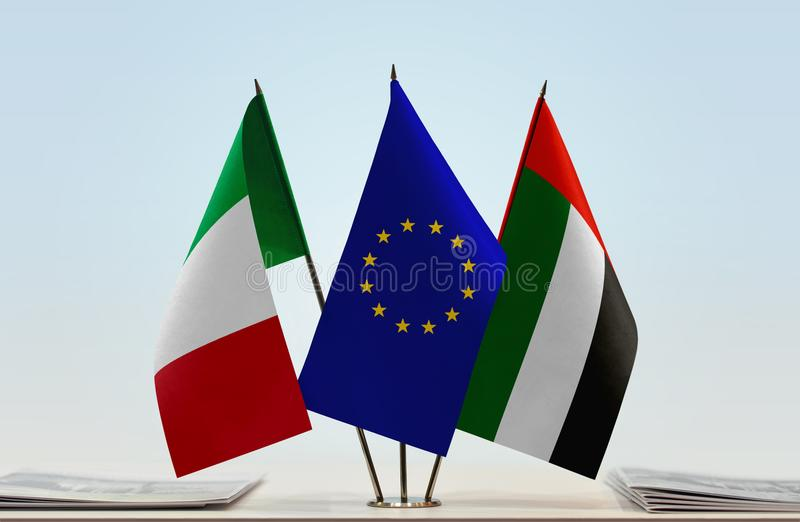 Flags of Italy EU and UAE. Desktop flags of Italy and UAE with European Union flag in the middle stock image