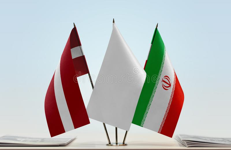Flags of Latvia and Iran. Desktop flags of Latvia and Iran with white flag in the middle royalty free stock photography