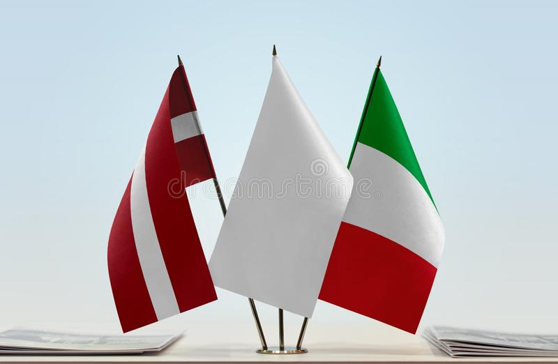 Flags of Latvia and Italy. Desktop flags of Latvia and Italy with a white flag in the middle royalty free stock photos