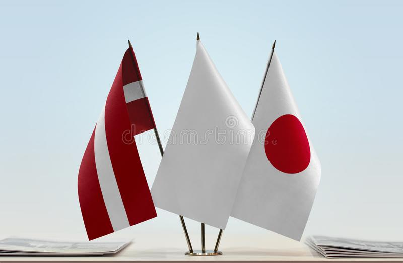 Flags of Latvia and Japan. Desktop flags of Latvia and Japan with white flag in the middle royalty free stock photography