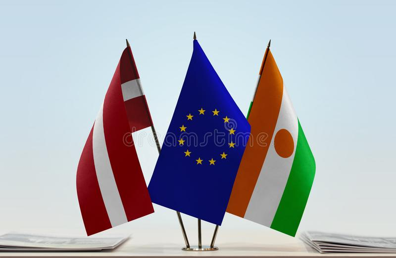 Flags of Latvia EU and Niger. Desktop flags of Latvia and Niger with European Union flag in the middle stock photography