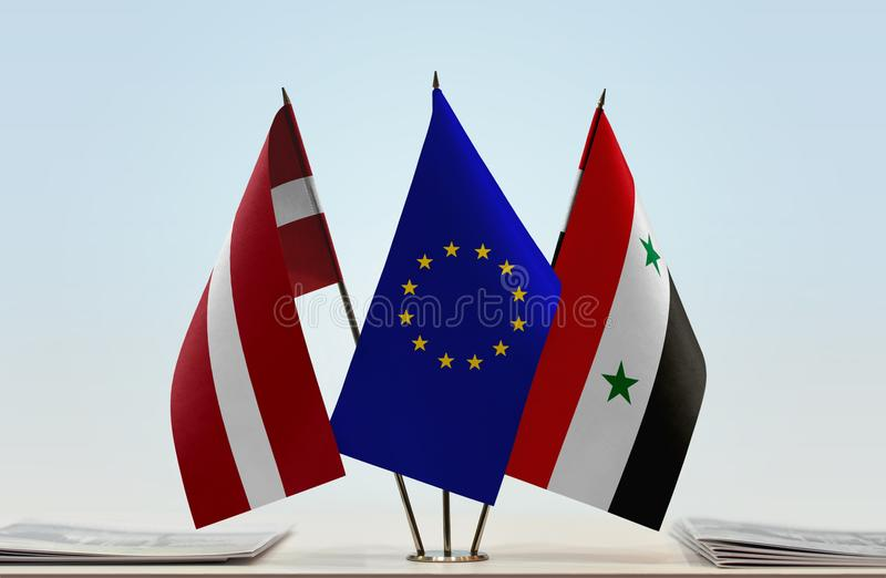 Flags of Latvia EU and Syria. Desktop flags of Latvia and Syria with European Union flag in the middle stock photo
