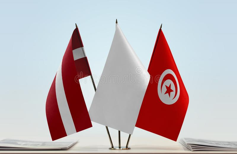Flags of Latvia and Tunisia. Desktop flags of Latvia and Tunisia with white flag in the middle royalty free stock image