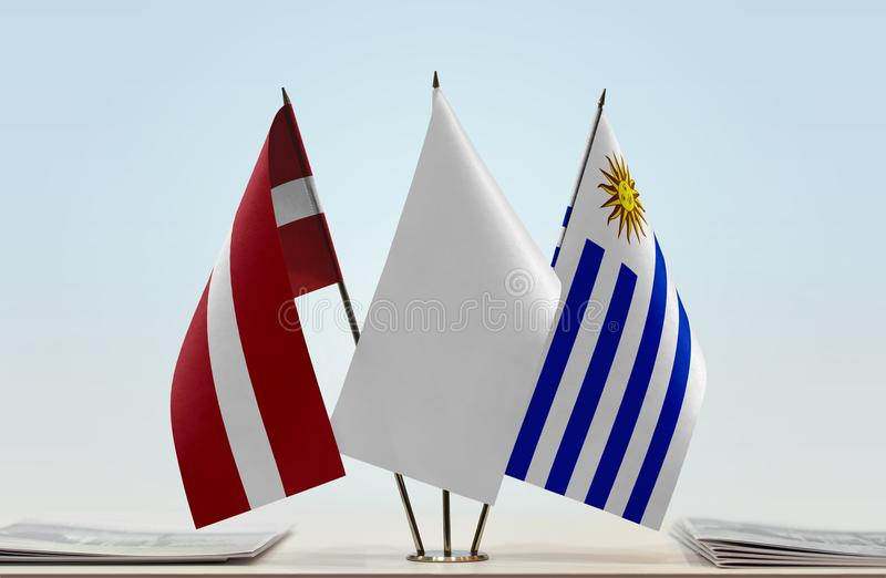 Flags of Latvia and Uruguay. Desktop flags of Latvia and Uruguay with white flag in the middle royalty free stock images
