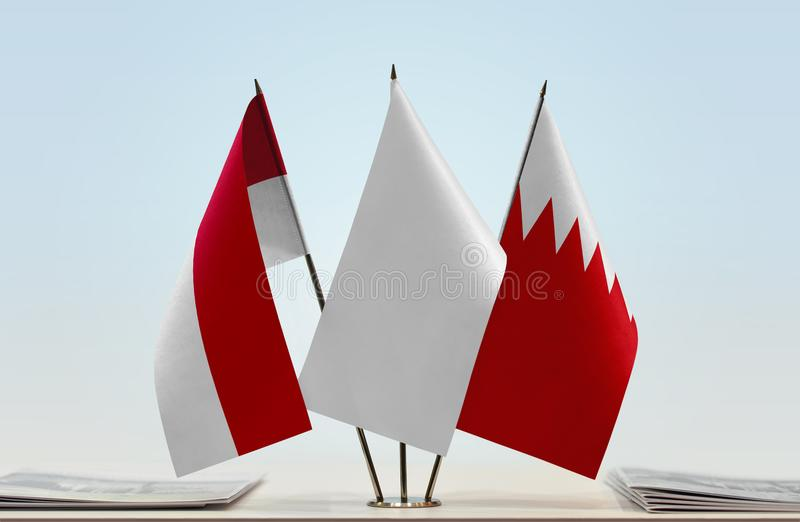 Flags of Monaco and Bahrain. Desktop flags of Monaco and Bahrain with white flag in the middle stock photo