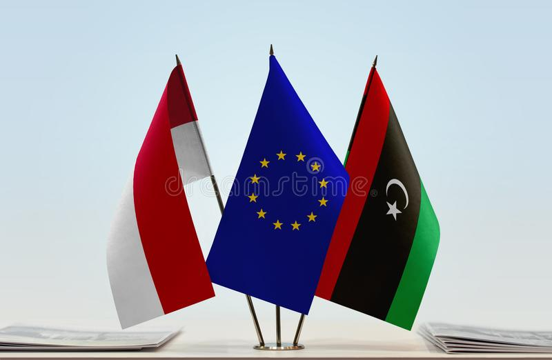 Flags of Monaco EU and Libya. Desktop flags of Monaco and Libya with European Union flag in the middle royalty free stock photo