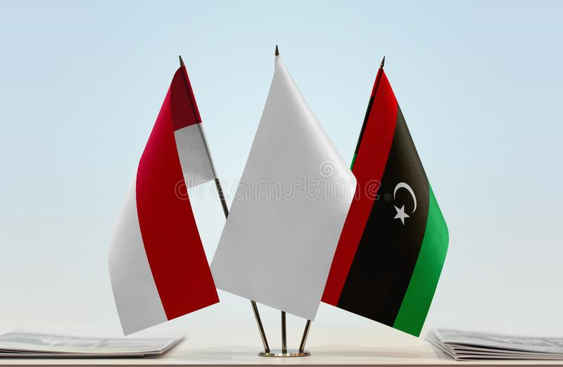 Flags of Monaco and Libya. Desktop flags of Monaco and Libya with white flag in the middle royalty free stock photography