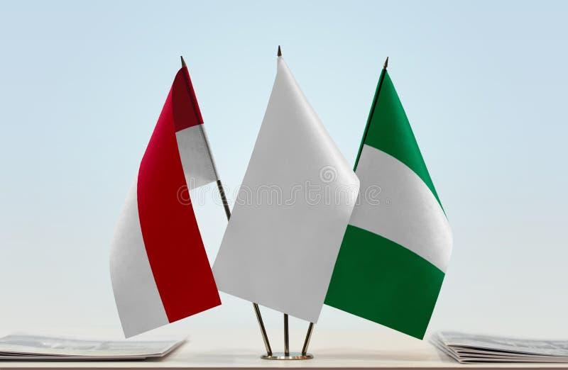Flags of Monaco and Nigeria. Desktop flags of Monaco and Nigeria with white flag in the middle royalty free stock photos
