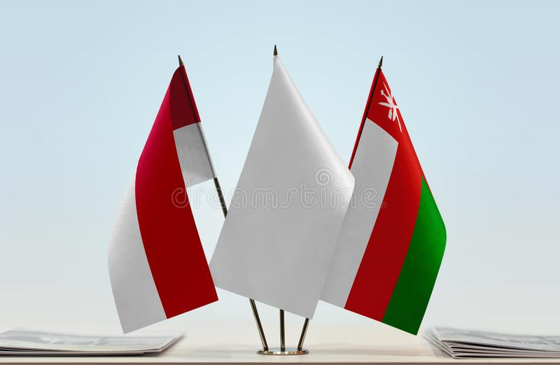 Flags of Monaco and Oman. Desktop flags of Monaco and Oman with white flag in the middle stock photos