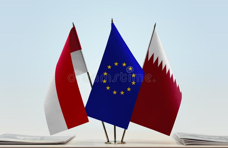 Flags of Monaco EU and Qatar. Desktop flags of Monaco and Qatar with European Union flag in the middle stock photos
