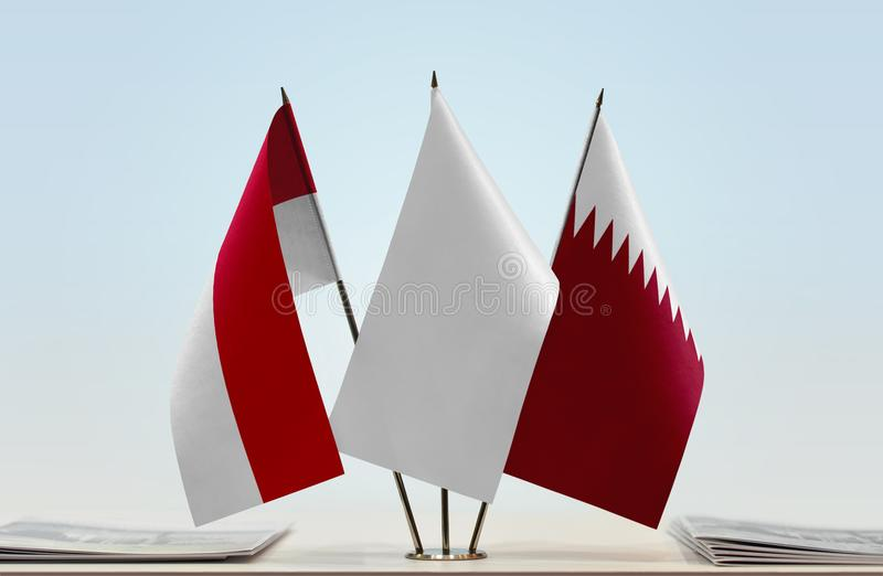 Flags of Monaco and Qatar. Desktop flags of Monaco and Qatar with white flag in the middle royalty free stock photos