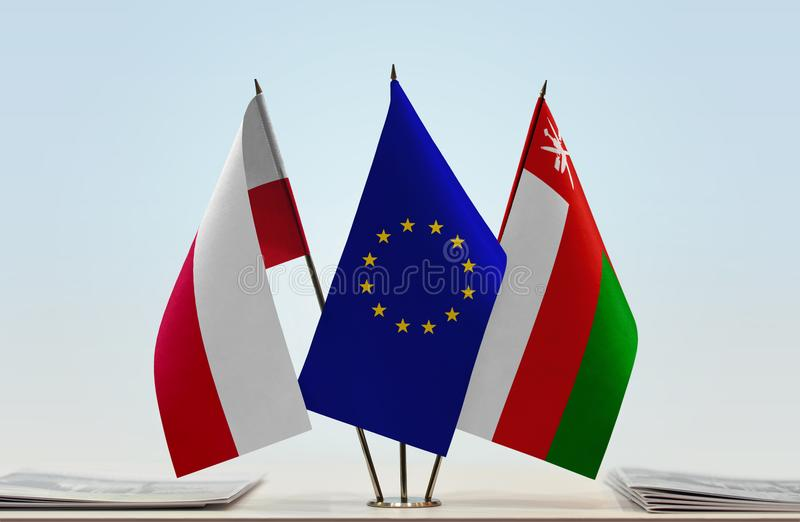 Flags of Poland EU and Oman. Desktop flags of Poland and Oman with European Union flag in the middle royalty free illustration