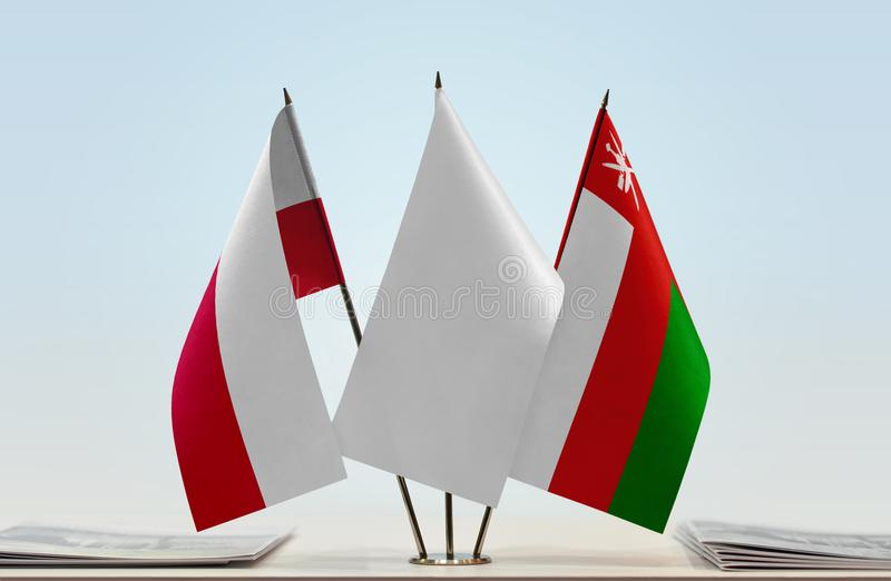 Flags of Poland and Oman. Desktop flags of Poland and Oman with white flag between royalty free stock image