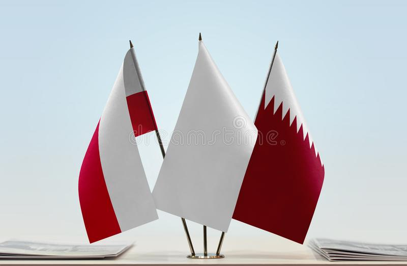 Flags of Poland and Qatar. Desktop flags of Poland and Qatar with white flag between stock image