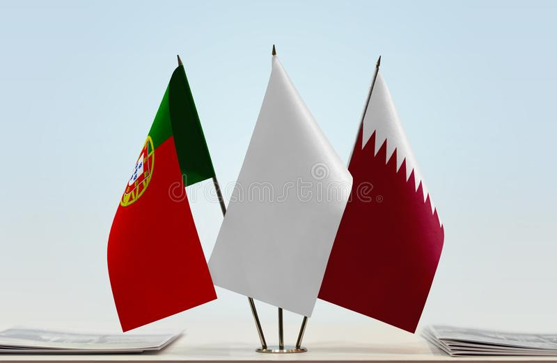 Flags of Portugal and Qatar. Desktop flags of Portugal and Qatar with white flag between royalty free stock photo