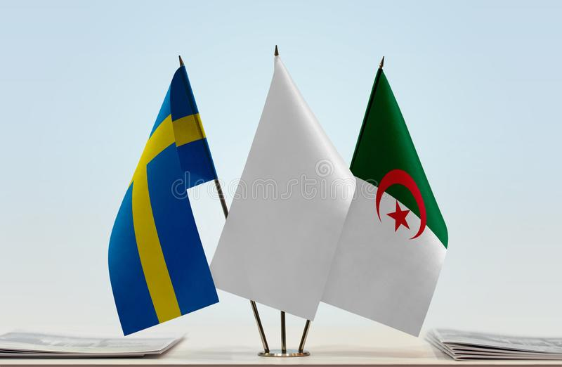 Flags of Sweden and Algeria. Desktop flags of Sweden and Algeria with white flag between stock images