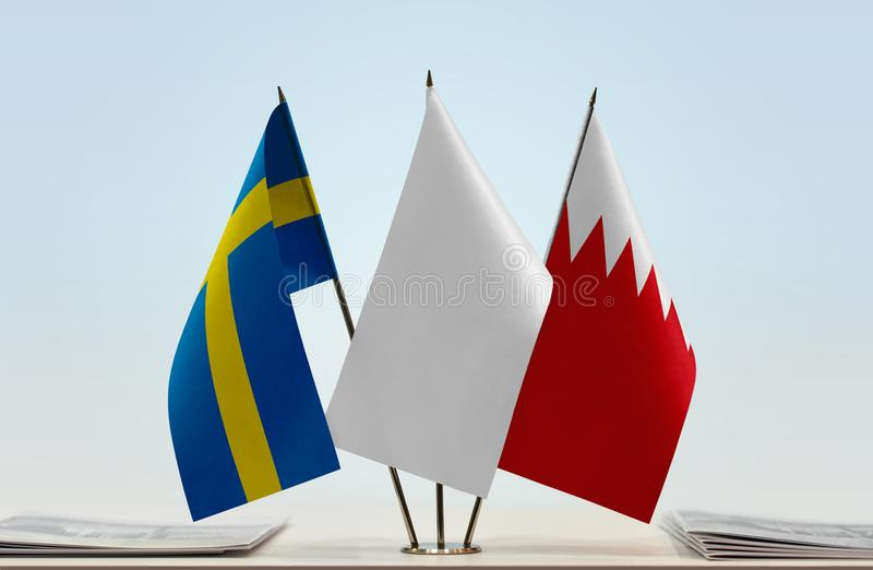 Flags of Sweden and Bahrain. Desktop flags of Sweden and Bahrain with white flag between royalty free stock images