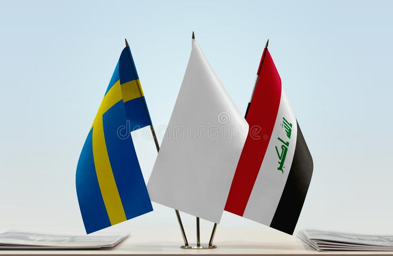 Flags of Sweden and Iraq. Desktop flags of Sweden and Iraq with white flag between stock photography
