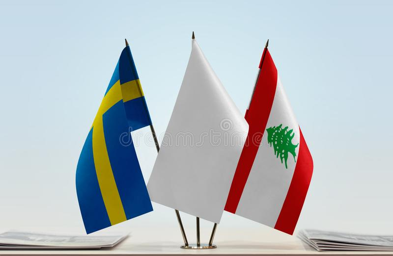 Flags of Sweden and Lebanon. Desktop flags of Sweden and Lebanon with white flag between stock photo