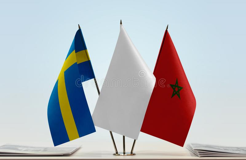 Flags of Sweden and Morocco. Desktop flags of Sweden and Morocco with white flag between stock photo