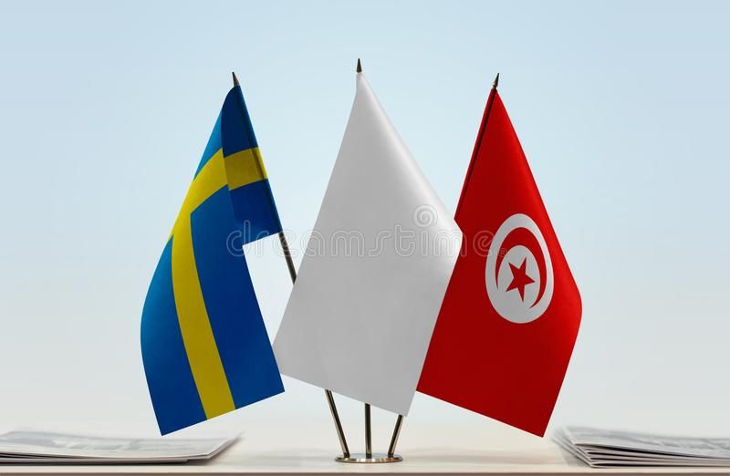 Flags of Sweden and Tunisia. Desktop flags of Sweden and Tunisia with white flag between royalty free stock image