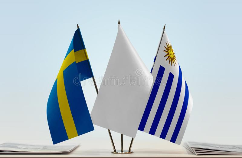 Flags of Sweden and Uruguay. Desktop flags of Sweden and Uruguay with white flag between royalty free stock images