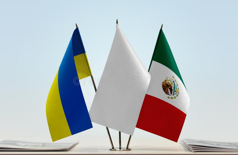 Flags of Ukraine and Mexico. Desktop flags of Ukraine and Mexico with white flag between stock photography