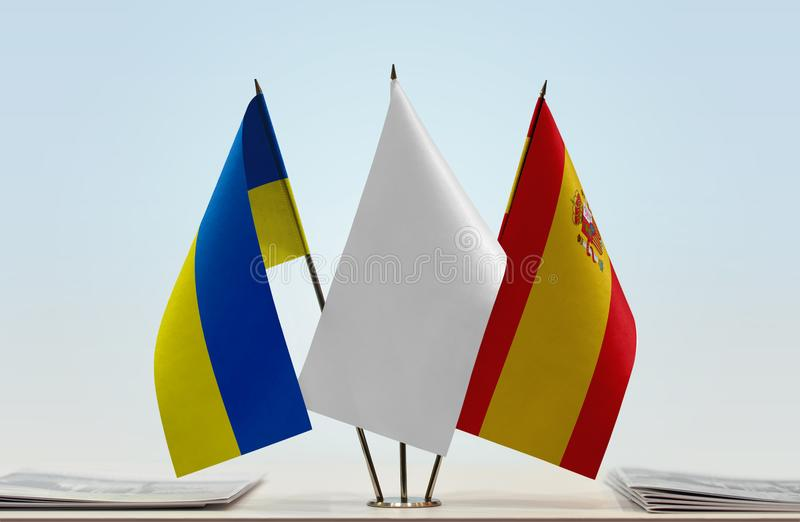 Flags of Ukraine and Spain. Desktop flags of Ukraine and Spain with a white flag in the middle royalty free stock photography
