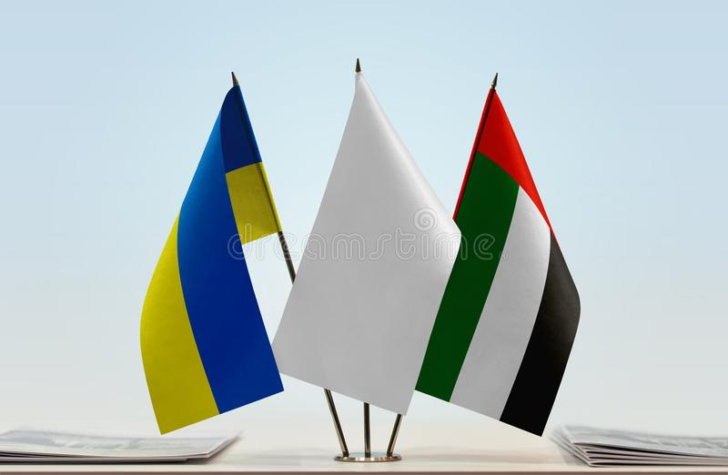 Flags of Ukraine and UAE. Desktop flags of Ukraine and UAE with white flag between royalty free stock images