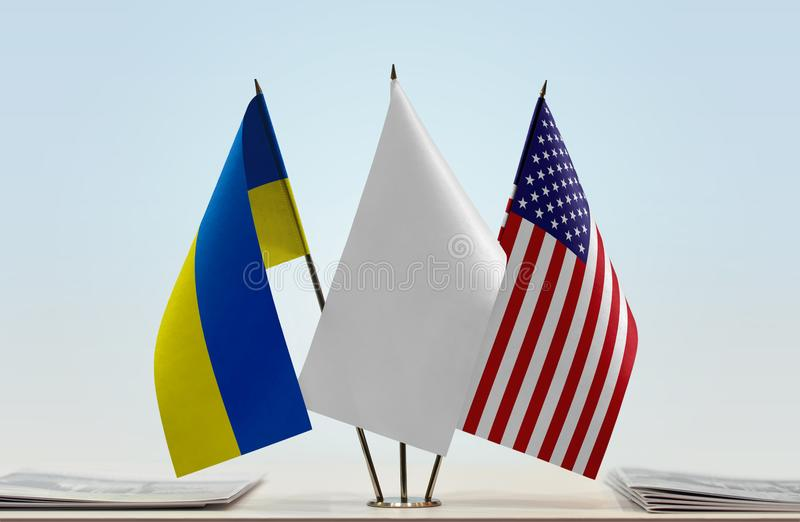 Flags of Ukraine and USA. Desktop flags of Ukraine and USA with white flag between stock photo