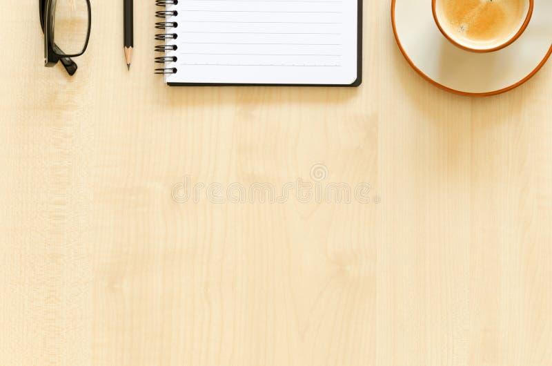 Desktop met notitieboekje, potlood, oogglazen en koffiekop stock afbeeldingen